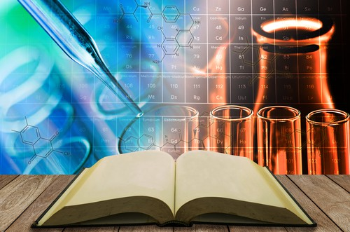 Image of an open book on a table with test tubes and beakers